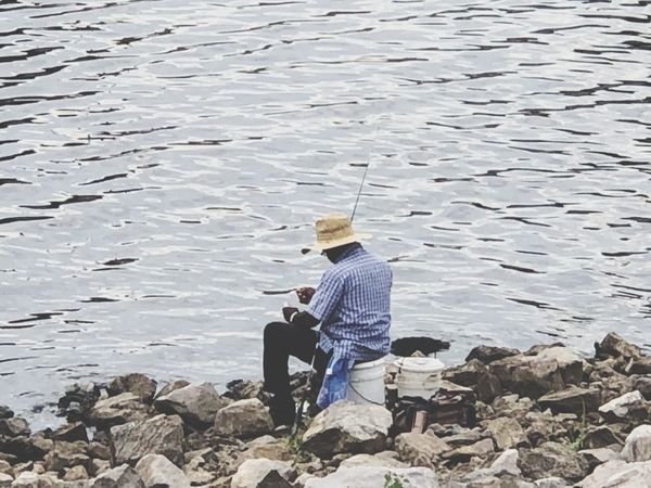 Fishing below the spillway Sitting Men Real People Adult Leisure Activity Casual Clothing Full Length Lifestyles Nature Seat Males  Water Solid Day
