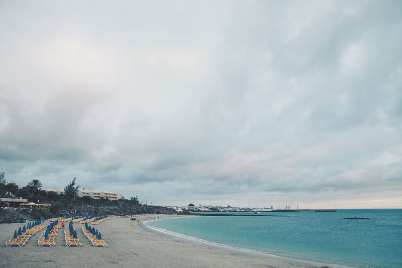 Lounge chairs and parasols arranged at beach against cloudy sky