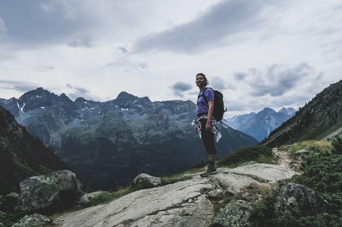 Admiring the view while hiking the Austrian Alps Adventure Backpack Beauty In Nature Casual Clothing Day Full Length Hiking Leisure Activity Lifestyles Mountain Mountain Range Nature One Person Outdoors People Real People Scenics Sky Standing Young Adult