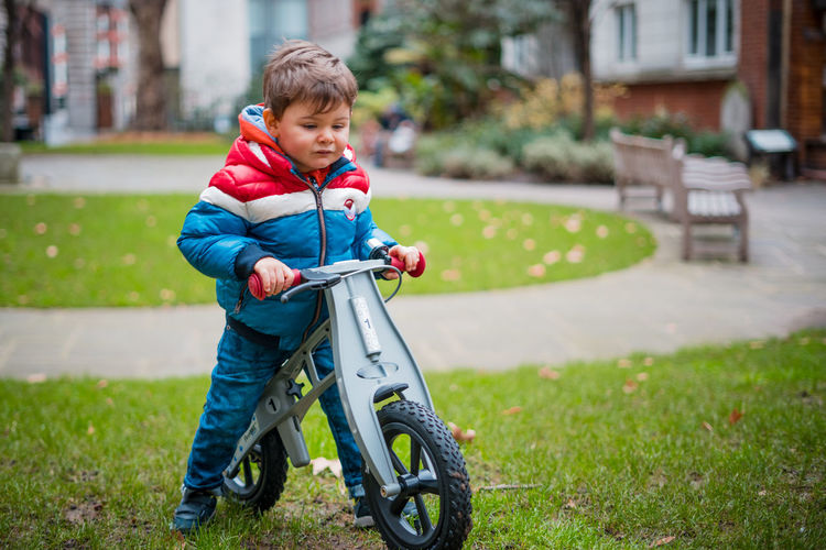 Boy with bicycle on grass