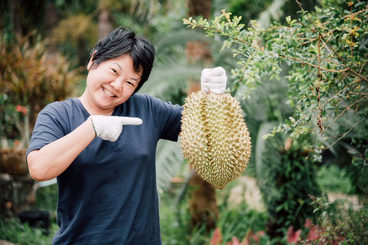 Portrait of happy mature woman holding durian