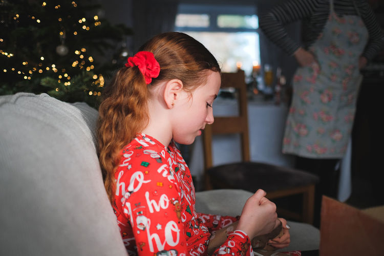 Mother and girl sitting on sofa at home