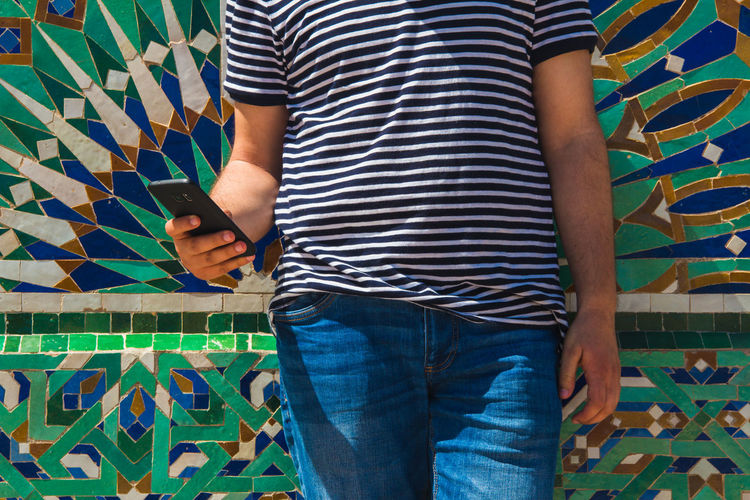 Midsection of man using mobile phone while standing against patterned wall