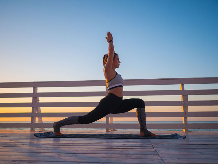 Full Length Of Woman Doing Yoga On Promenade During Sunrise
