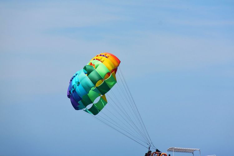 A bright colourful parasailing Blue Flying Freedom Multi Colored Day Sky Outdoors Celebration Adventure Hot Air Balloon Close-up No People Amusement Park Ballooning Festival Fun Parasailing First Eyeem Photo