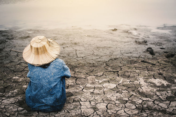 Rear view of girl sitting by pond on drought field