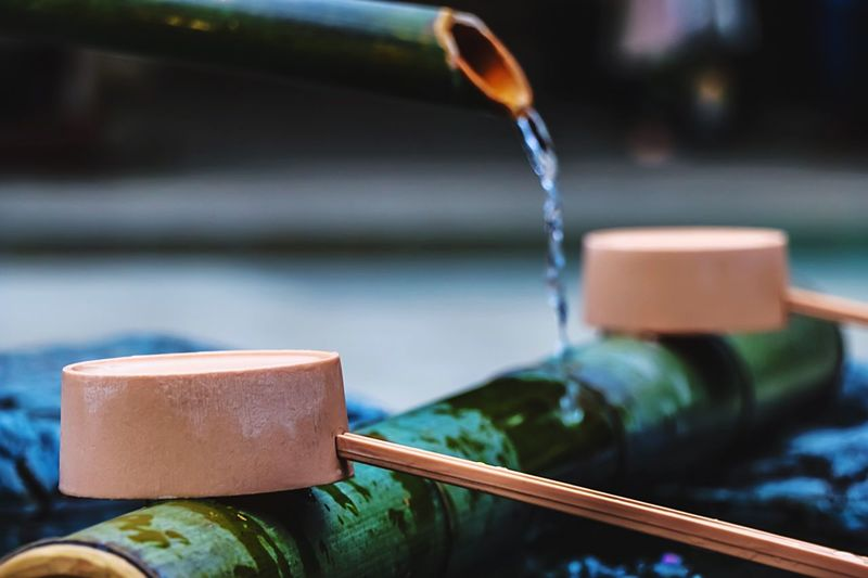 Close-up of wooden ladles on bamboo at drinking fountain
