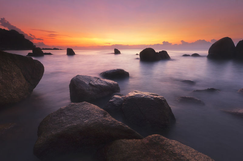A moment of calm and serene captured in the morning at the beach. Beauty In Nature Day Horizon Over Water Idyllic Nature No People Outdoors Rock - Object Scenics Sea Sky Sunset Tranquil Scene Tranquility Travel, Sea, Ocean, Water, Beach, Sky, Sunrise, Summer, Vacation, Silhouette, Beautiful, Colorful, Tourism, Sunset, Landscape, Coast, Outdoor, Nature, Honeymoon, View, Caribbean, Destination, Romantic, Pacific, Tropical, Reflection, Sand, Scenic, Horizon, Water