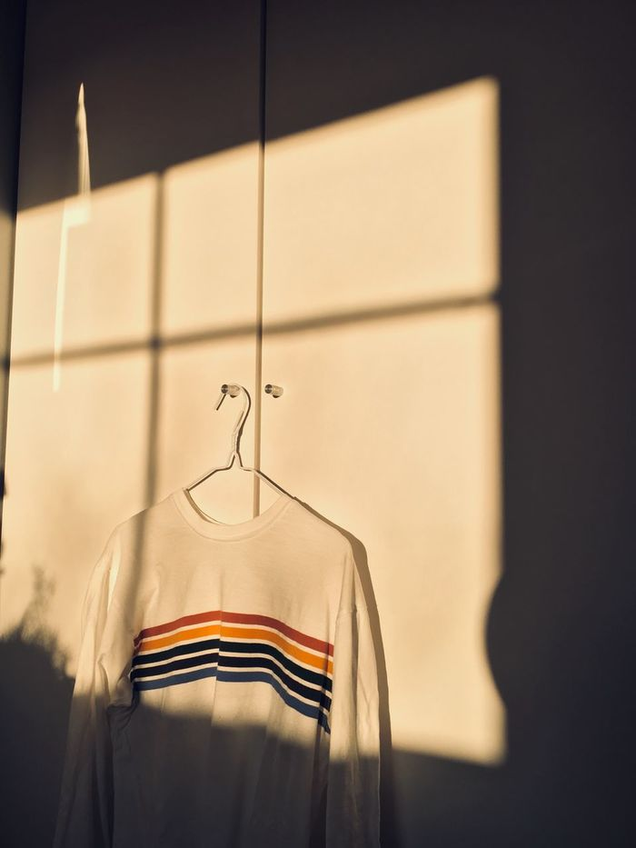 Close-up of rainbow sweater hanging on wall at home