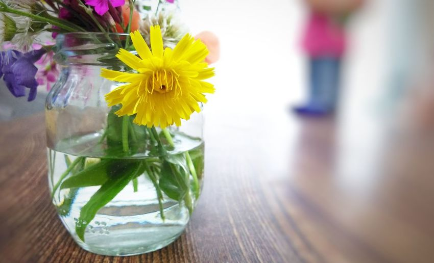Close-up of yellow flower in glass vase on table