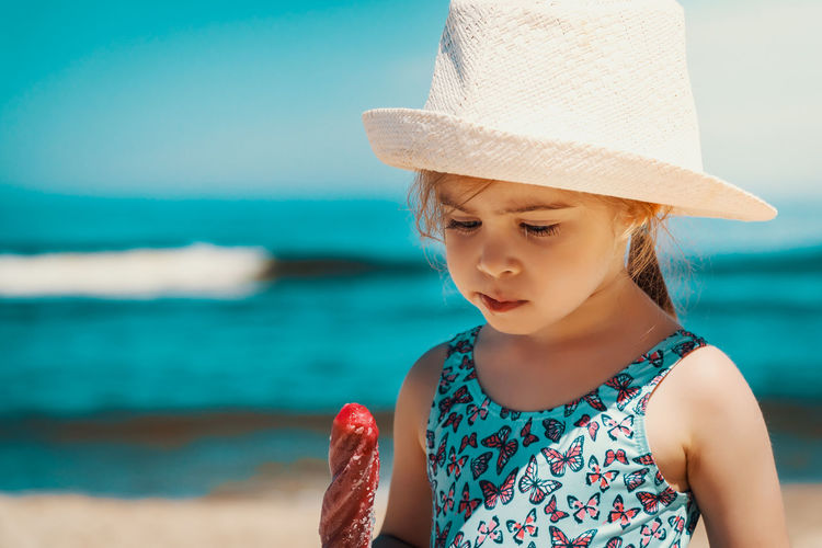 Summer Child Girl Kid Sea Beach Water Sky Ice Cream Childhood Hat Leisure Activity One Person Girls Casual Clothing Focus On Foreground Land Front View Day Lifestyles Women Real People Innocence Outdoors Horizon Over Water Sun Hat