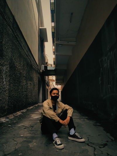 Portrait of young man sitting on alley amidst buildings