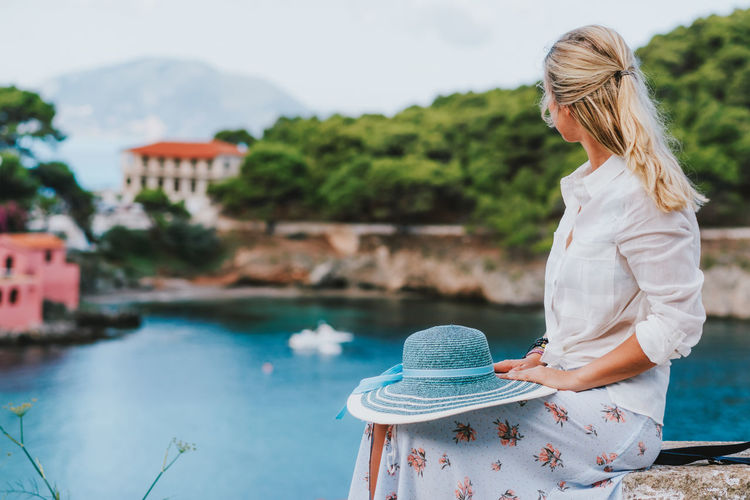 Woman holding hat looking at lake while sitting on retaining wall