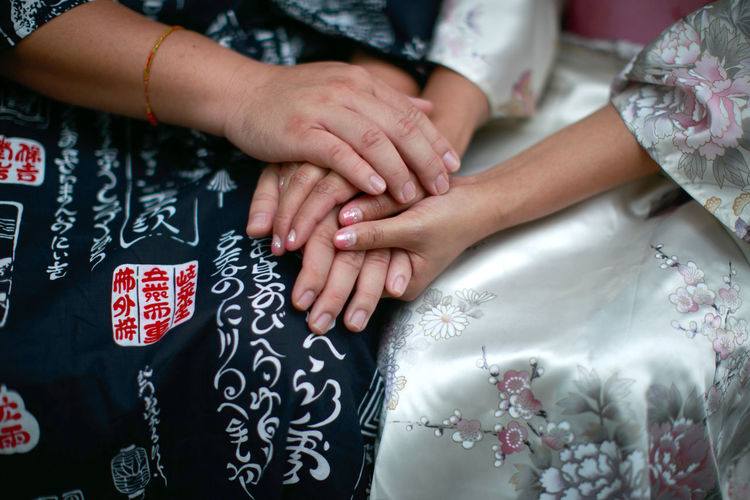 Midsection of women holding hands