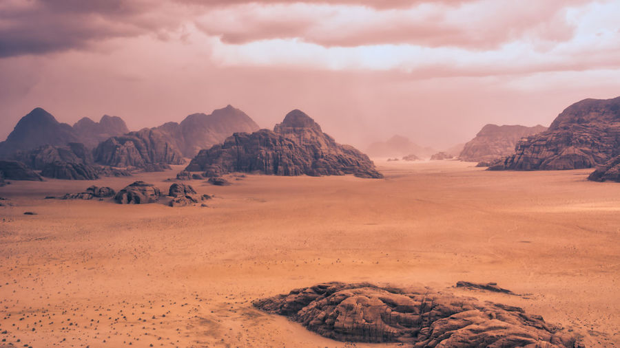Storm and rain clouds over the desert landscape of wadi rum in jordan. panoramic shot