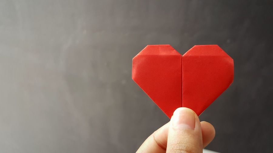 Cropped hand of woman holding paper heart shape against wall