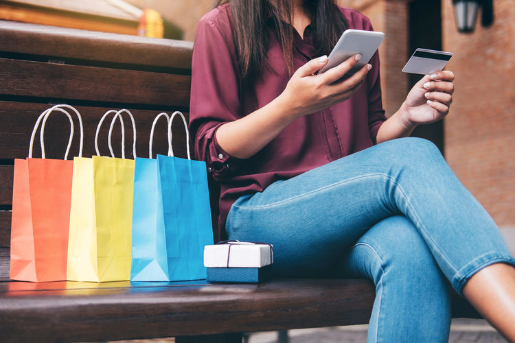 Midsection Of Woman Using Smart Phone For Online Shopping