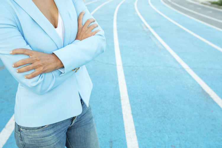 Close up portrait of business woman while standing with arms crossed on a athletics court One Person Midsection Real People Day Sport Lifestyles Hand Human Hand Track And Field Men Standing Front View Outdoors Human Body Part Focus On Foreground Running Track Sports Clothing Casual Clothing Leisure Activity