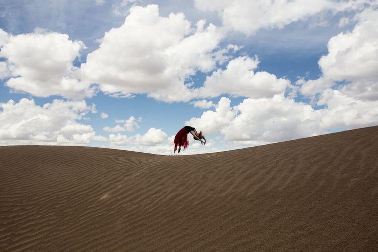 Teenage girls jumping on sand against sky