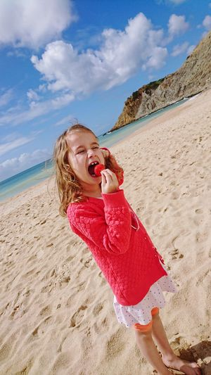 Girl Eating Strawberry While Standing At Beach Against Sky During Sunny Day