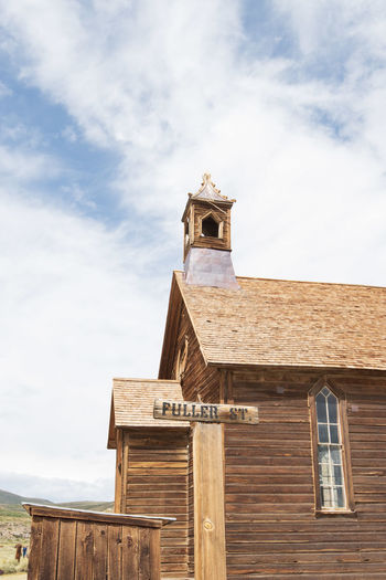 Low angle view of old church building against sky with wooden street sign in ghost town