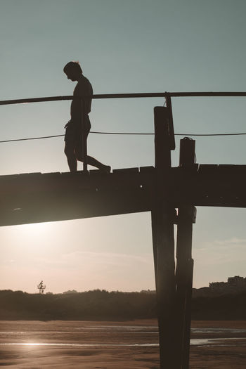 Walking to the sea Silhouette Summer Views Summertime Sunlight Sunset_collection The Traveler - 2018 EyeEm Awards Bridge Bridge - Man Made Structure Clear Sky Connection Full Length Lifestyles Nature One Person Outdoors Real People Shadow Silhouette Sky Standing Summer Sun Sunrise Sunset Water