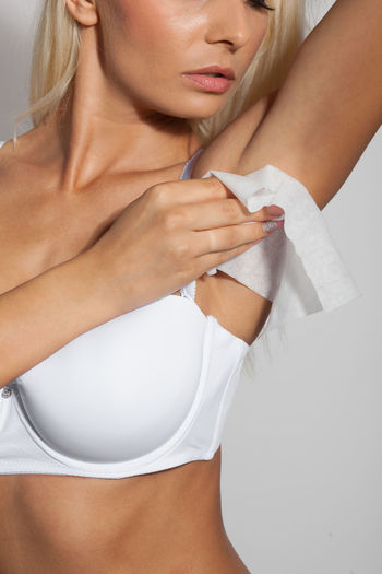 Midsection of female model in lingerie wiping under the arm against white background
