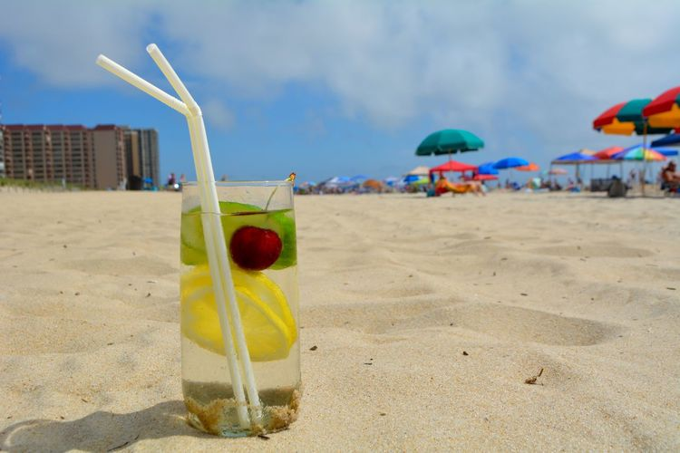 Close-up of drink on beach against sky