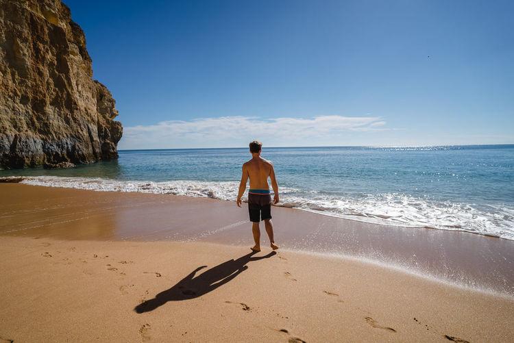 Rear View Of Shirtless Man Walking At Beach Against Sky
