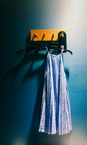Blue Dress Hanging On Coathanger From Hook On Wall