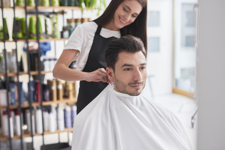 Female hairdresser draping cap to man sitting on chair