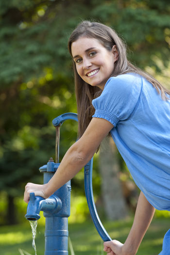 young beautiful woman gardening Cheerful Day Drinking Drinking Fountain Drinking Water Faucet Filling Focus On Foreground Happiness Irrigation Equipment Lifestyles Looking At Camera Motion One Person Outdoors Pipe - Tube Portrait Real People Side View Smiling Spraying Washing Water Young Adult Young Women