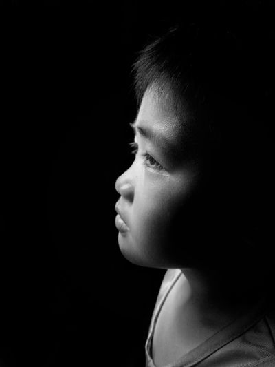 Close-up of boy looking away in darkroom