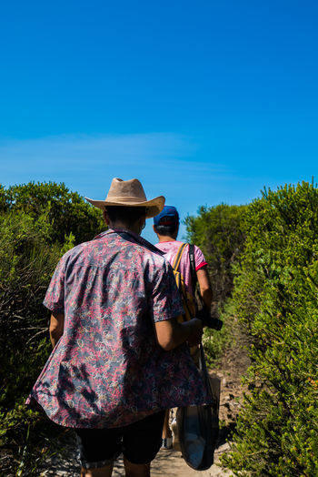 Rear view of man and woman walking amidst plants against sky