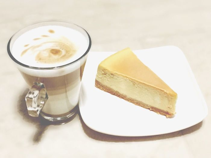 Close-Up Of Coffee Latte And Caramel Cheesecake