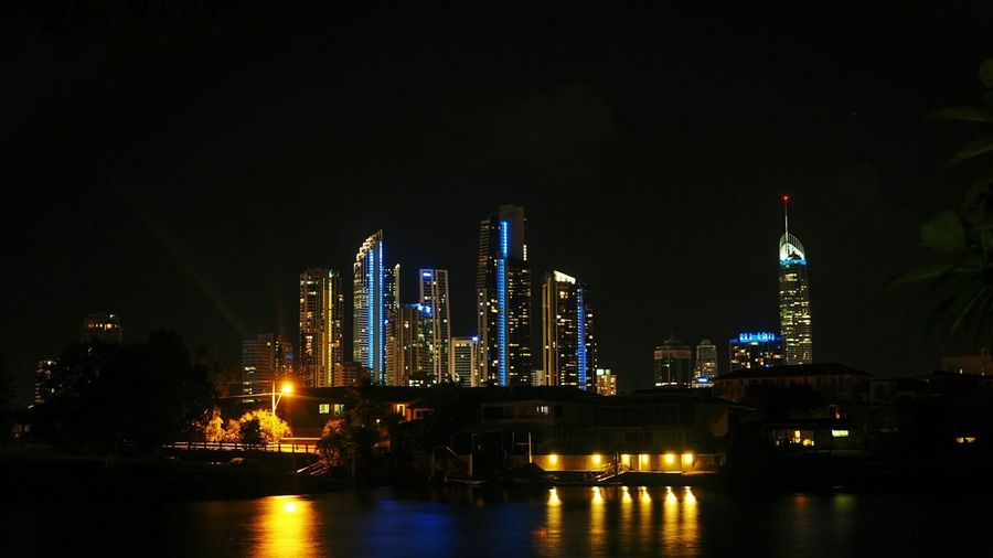Lake In Front Of Illuminated Buildings Against Sky At Night