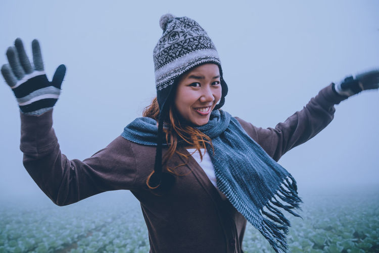 Portrait of cheerful young woman standing at farm during foggy weather