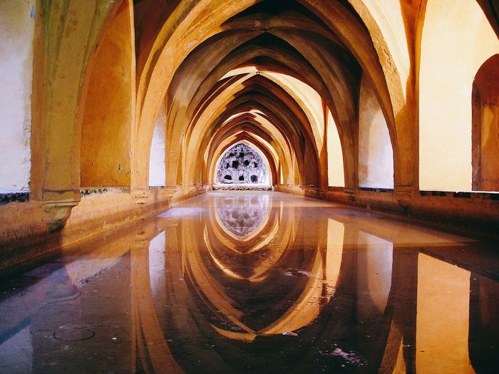 Reflection of ribbed vault on corridor filled with water