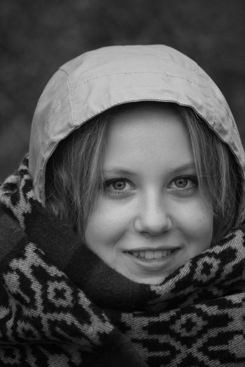 Close-up portrait of smiling young woman wearing hood