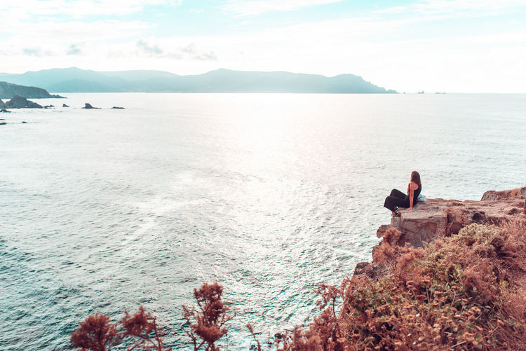 Full length of woman sitting by cliff against sea