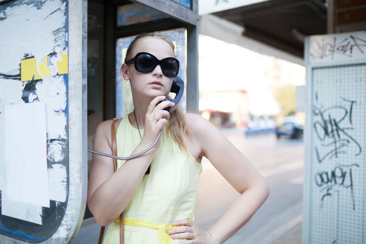Woman in sunglass talking on pay phone