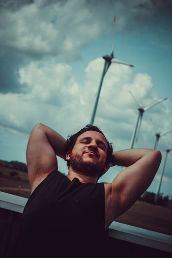 Low angle view of man looking away against sky relaxing and streching