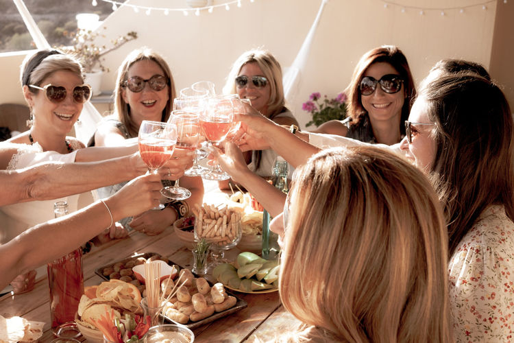 Group of cheerful women in friendship enjoying party for birthday. Wooden table. Wineglass for celebrate and large smiles. Nine people Active Adult Appetizer Background Beautiful Blonde Bonding Bread Bright Casual Caucasian Celebrating Celebration Cheerful Cheese Eating Enjoying Exuberant Fashionable Females Food Friends Friendship Funny Glasses Group Hammock Happiness Happy Holiday Meal Merry Nine Olives People Persons Radiant Red Wine Smiling Sunglasses Sunset Table Terrace Toast Toasting Togetherness Vegetables Wall Women Wood