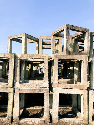 Low angle view of abandoned built structure against blue sky