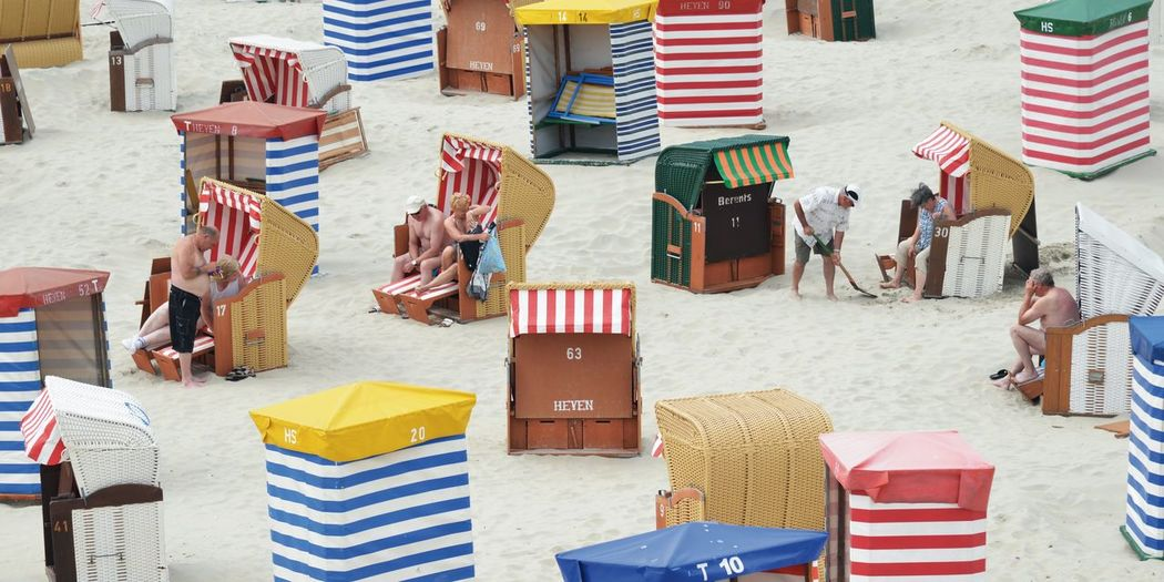 older people enjoy the beach of Borkum Group Of People Adult Day Women Men Real People People Striped Standing Group Outdoors Table Young Women Borkum Older People Sand Beach Chairs In Germany Fun Colorful Way Of Life Playground Shovel To Dig Streetartphotography Narrative