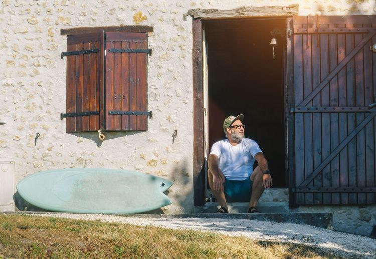 Portrait of man sitting at doorway