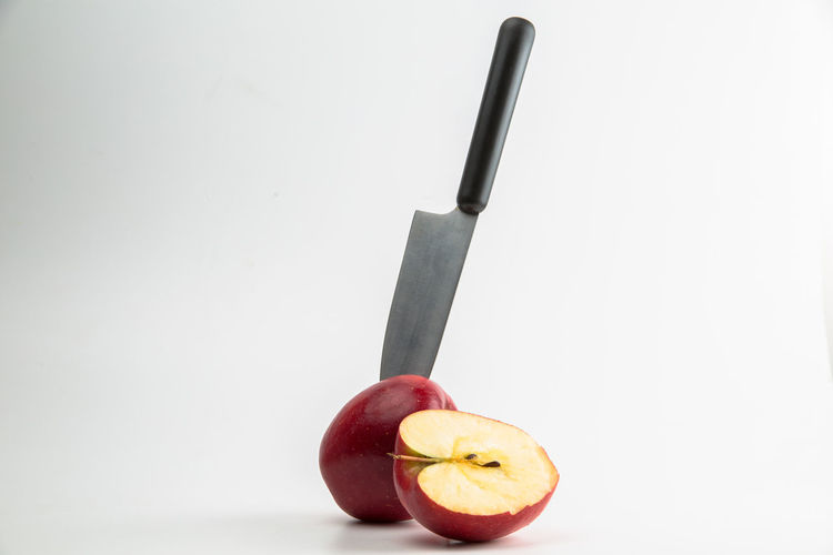 Fruit Food And Drink Food Healthy Eating Apple - Fruit Kitchen Knife Wellbeing Indoors  Freshness Studio Shot Still Life White Background Copy Space No People Close-up Single Object Table Red Knife Orange Color Orange Table Knife Temptation Healthy Lifestyle Diet & Fitness