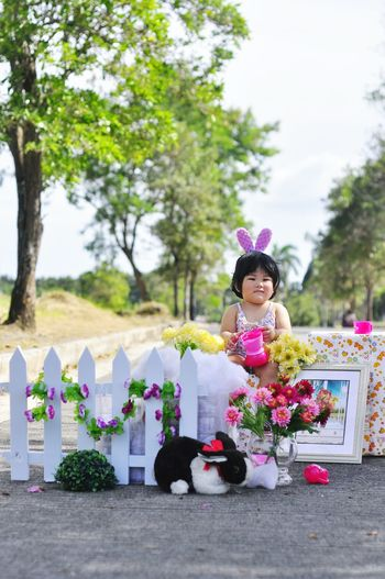 Cute baby girl with gifts and toys sitting outdoors