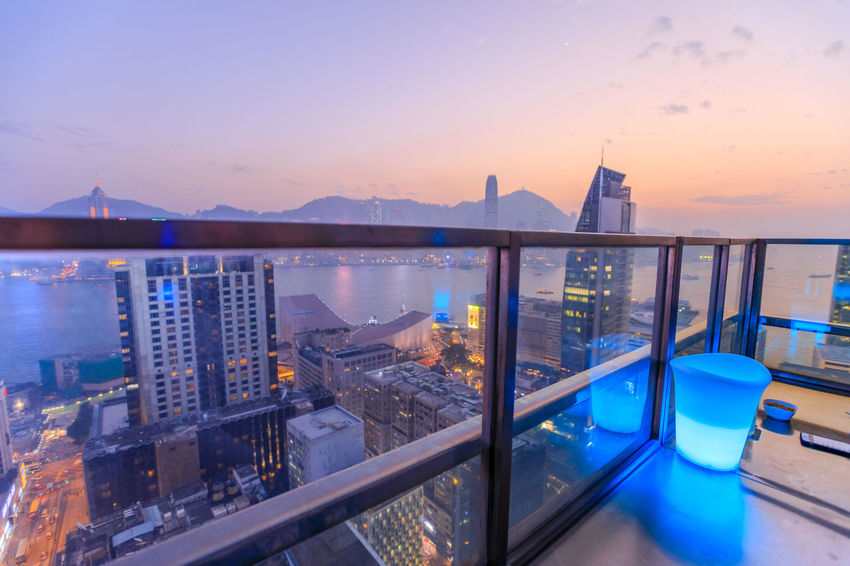 Hong Kong, China - January 1, 2016: spectacular aerial view of Victoria Harbor skyline at sunset from the rooftop of Eye Bar, a modern skybar inside iSquare shopping center in Kowloon, Hong Kong city. HongKong Hong Kong City Hong Kong Sunset Skyline Night Cityscape Business Aerial View Light Show Laser Show Skyscraper Victoria Harbor Panorama Drink Architecture Sky Water Built Structure Building Exterior Nature Mountain City No People Orange Color Illuminated Building Reflection Beauty In Nature Scenics - Nature Travel Destinations Sea Outdoors Glass Bay