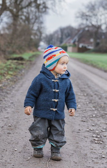Toddler girl on footpath – Kempen, Germany Females Girl Girls Toddler  Toddlerlife Adventure Baby Babyhood Babygirl Boots Building Exterior House Germany Caucasian Cheerful Coat Duffle Coat Wool Curiosity Cute Diminishing Perspective Dirt Dirty Exploring Field First Steps Footpath Front View Happiness Hiking Jacket Joy Looking Away Messy Mud Muddy Nature Pants Trousers Portrait Rural Scene Tree Bare Tree Walking Wanderlust Weather Knit Hat Toggle Button Discovery Solitude Child Childhood One Person Clothing Real People Men Full Length Winter Males  Casual Clothing Boys Warm Clothing Leisure Activity Focus On Foreground Standing Day Lifestyles Innocence Outdoors